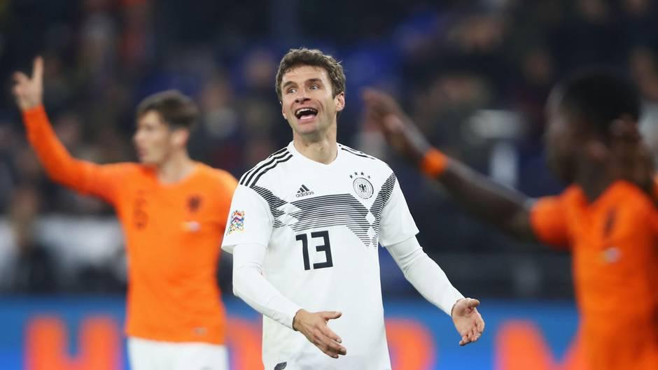 Thomas Müller gestikuliert im DFB-Trikot auf dem Platz. Im Hintergrund stehen zwei Spieler der Niederlande