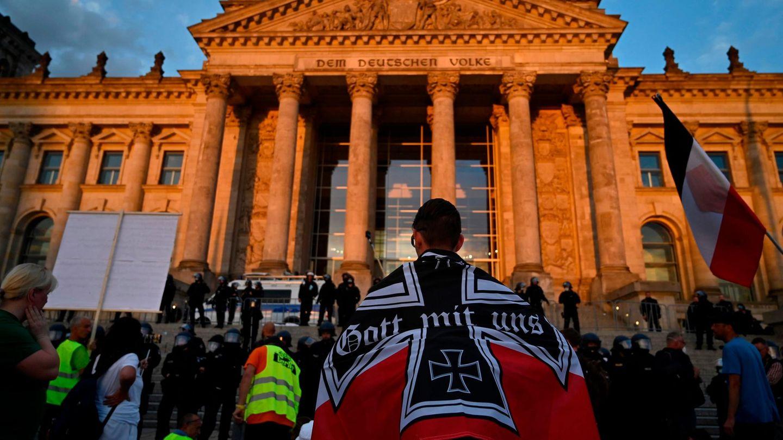 Berlin: Ein Demonstrant, eingewickelt in eine schwarz-weiß-rote kaiserliche Reichsflagge, vor dem Reichstagsgebäude