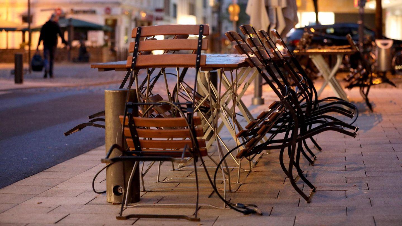 Stühle und Tische sind am Morgen vor einer Gaststätte in Köln zusammengestellt