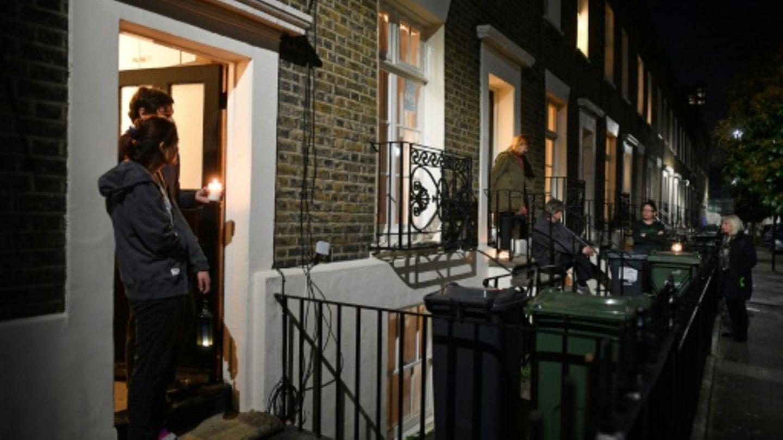 Menschen in London treten mit Lichtern vor ihre Türen