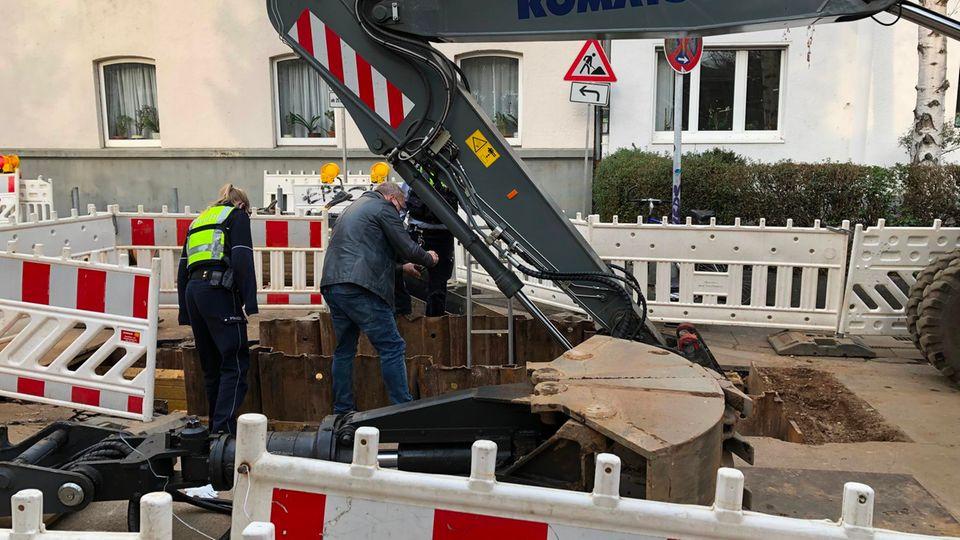 Polizisten stehen an einer Tiefbaustelle, an der ein Arbeiter zuvor bei einem Unfall lebensgefährlich verletzt worden war.