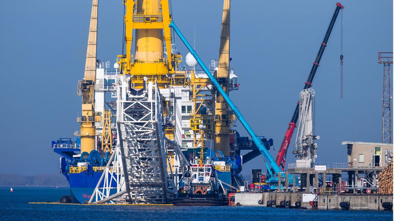 """Ein Schlepper liegt hinter dem russischen Rohr-Verlegeschiff """"Akademik Tscherski"""" im Seehafen. Das Spezialschiff wird derzeit mit weiterer Technik ausgerüstet."""