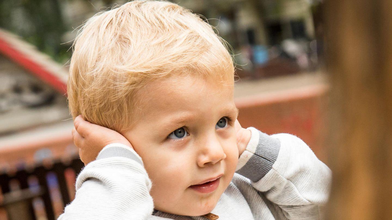 Ein kleiner Junge hält sich die Ohren zu