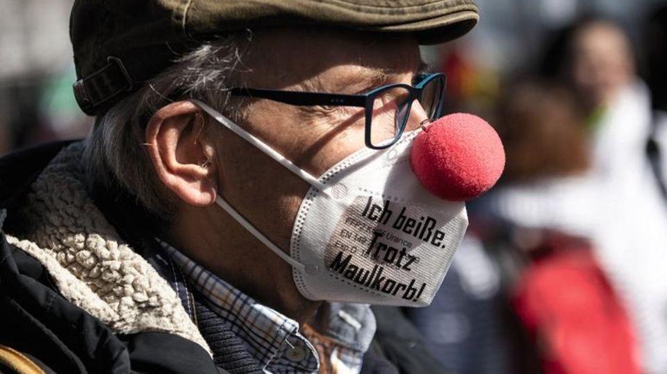 Jemand, der sich für einschlägig informiert halten mag: Querdenker- Clown bei einer Demonstration in Kassel