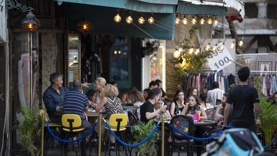 Menschen genießen ihre Zeit in einem Café: Das Tragen von Masken ist in Israel nach einem Rückgang der Infektionsraten in Tel Aviv nicht mehr erforderlich ist