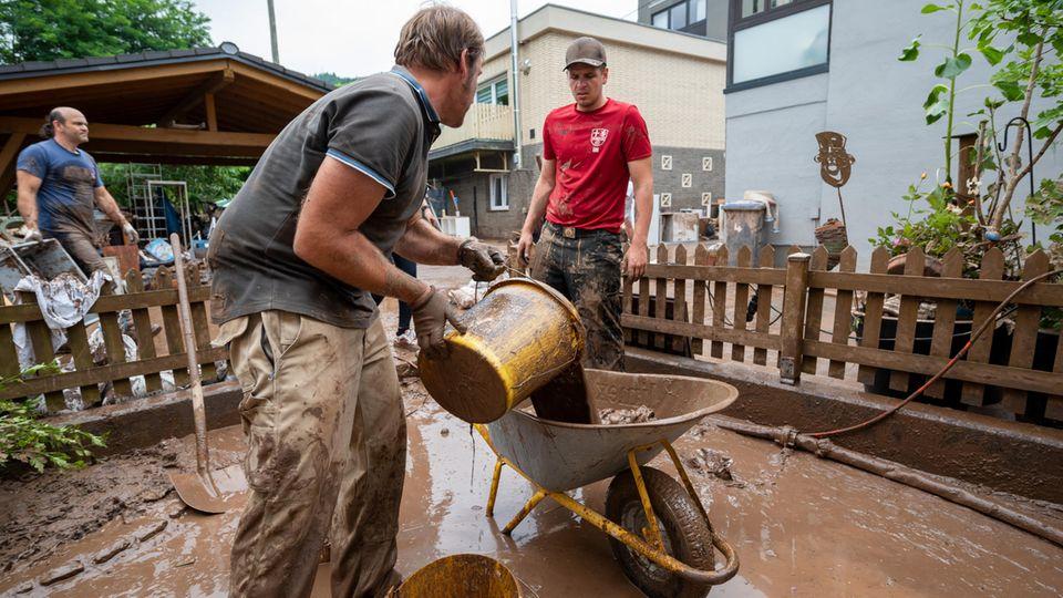 Das große Aufräumen in Kordel:Mit Eimern und Schubkarre entsorgen Anwohner die Schlammmassen nach dem Hochwasser der Kyll inRheinland-Pfalz